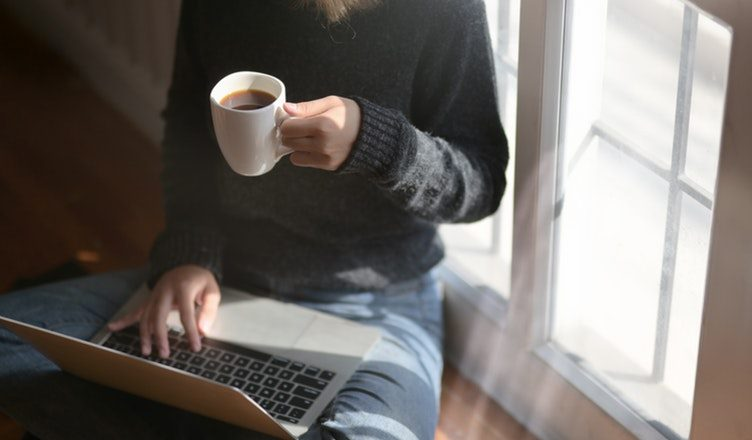 Kvinde med computer og kop kaffe